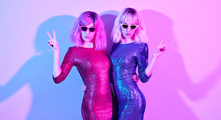 Gorgeous model woman in fashionable party outfit with Kiss Face expression, peace sign.Two Playful Sisters dance, Pink Blonde Dyed Hair. Colorful light, High Fashion.