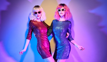 Wall Mural - Sexy woman in Party bright Luxury outfit dance. Music vibrations. High Fashion. Two Model girl with Pink Blonde Dyed Hair, makeup. Colorful neon light. Creative Art Style