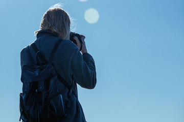 A female photographer is holding a camera.