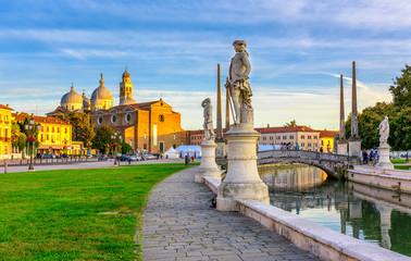 View of canal with statues on square Prato della Valle and Basilica Santa Giustina in Padova (Padua), Veneto, Italy