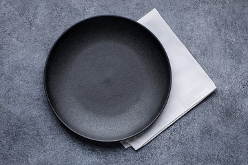 Empty black plate and white napkin on gray concrete background. Top view, with copy space