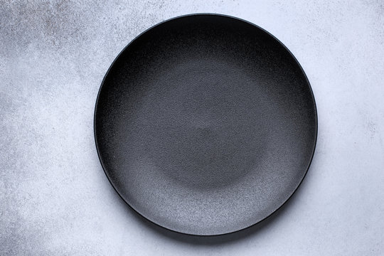 Empty black plate on gray concrete background. Top view, with copy space