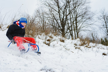 for a sledge down the boy in red pants is very happy