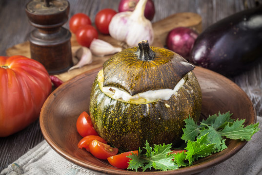 Baked round squash stuffed with vegetables in plate