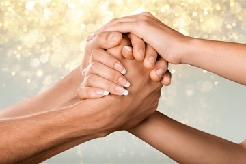Female and male hands holding each other on background