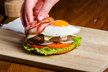 The process of making juicy fresh sesame burgers with beef, meat, cheese, tomatoes, sauce, pineapple, fresh greens, eggs, mushrooms, mushrooms, onions, peppers on a kitchen chopping board with differe