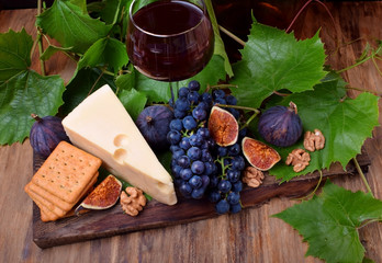Red wine in a glass surrounded by the appetizers: Maasdam cheese, figs, walnuts and a bunch of Isabella grapes on a wooden board