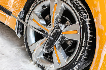 Yellow car wheel washed in self service carwash, brush cleaning aluminium rim disc covered in shampoo
