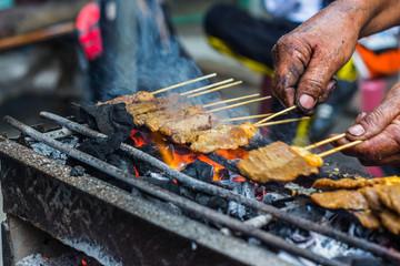 Man roast meat steak thai style on charcoal stove.