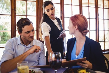 Business people discussing menu card with waitress