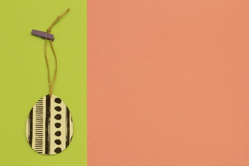 Decorated original egg on jute cord with clothespin on contrasting light green and terracotta background. Minimalism style.