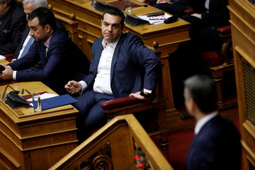 Greek PM Tsipras looks at New Democracy party leader Kyriakos Mitsotakis addressing lawmakers during a parliamentary session before a confidence vote in Athens