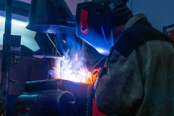 Welding work. Welder in a protective mask. Welding metal. Heavy industry. A man works on a welding machine.