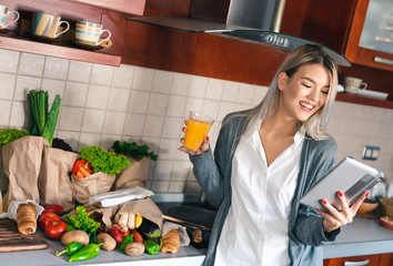 Young happy woman using tablet while drinking orange juice in kitchen