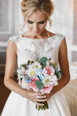Fashionable and elegant blonde model girl with stylish wedding hairstyle and with bright makeup in lace white dress with the big luxury bouquet of exotic flowers in her hands posing at interior