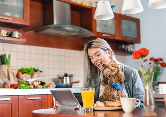 Young happy woman sitting at table and using tablet while holding a dog in her lap in kitchen