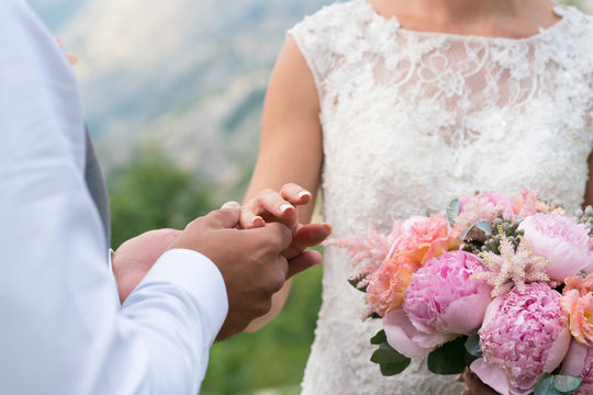 the groom puts the ring on the bride's finger