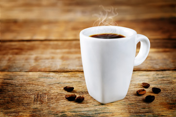 Cup of hot strong coffee with coffee beans