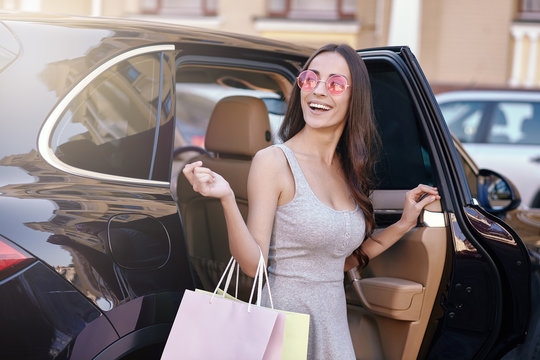 woman getting out of the car with shopping bags