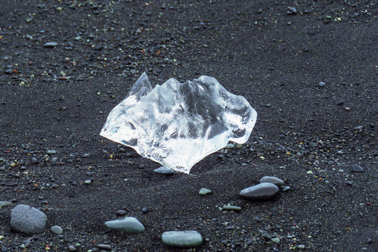 Chunk of ice looking like a precious stone on the.black sand of Diamond Beach at Jökulsárlón glacier lagoon, Jokulsarlon, Iceland
