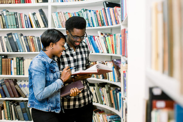 Afro-American girl and black guy surrounded by books in library. Students are looking for books.