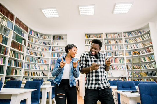 Beautiful African-American cheerful couple of students have a fun and dancing in the library. The girl smiles and the boy dances while listening to music. Happy couple smiling and dancing in library