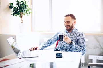 Caucasian happy smiling businessman working on laptop in his office