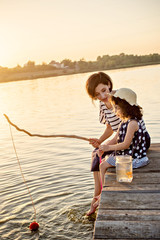 Mom and her little daughter are fishing with a fishing rod on a pier at sunset by the lake.