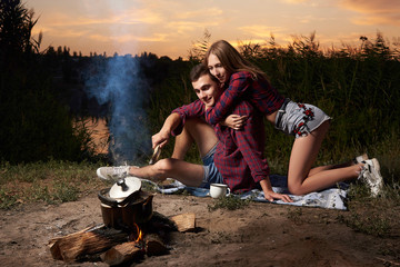 Romantic couple in love late in the evening by the fire on the lake.