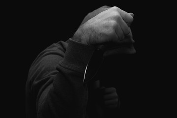 man in a jacket with a hood with a knife in his hand