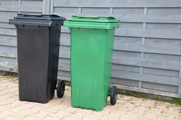 black and green plastic garbage bin in street for recycling concepts and designs