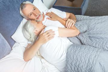man hugging woman sleeping on his shoulder
