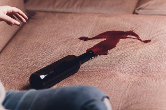 Red wine spilled on a brown couch sofa. dark bottle of red wine dropped
