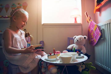 Cute girl playing tea-party with her toys