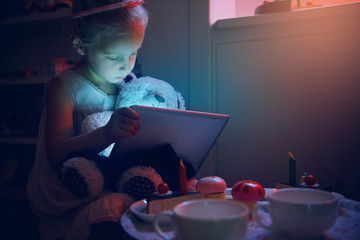 Little girl holding tablet and toy bear