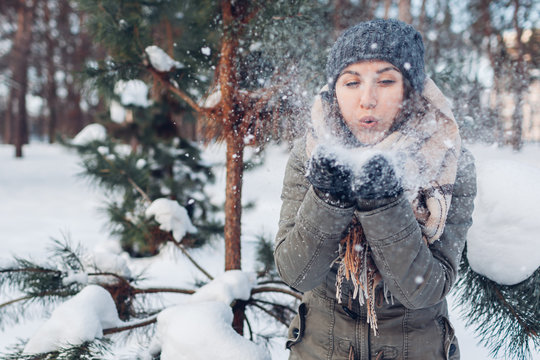 Young woman blowing snow in winter forest. Girl having fun outdoors