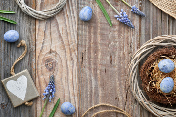 Easter background with eggs, blue hyacinth flowers and  wooden heart, top view on rustic wood, copy-space