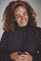 Laughing female entrepreneur using her cellphone against a gray