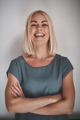 Laughing entrepreneur with her arms crossed against a gray backg