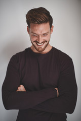 Young male entrepreneur laughing while standing against a gray b