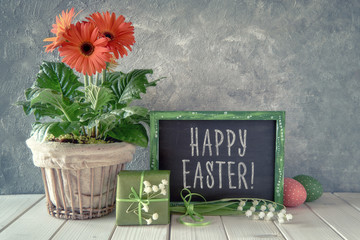 Spring flowers, Easter decorations and a blackboard on white table, greetings on a blackboard