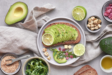 Green salad and avocado sandwich, top view on grey stone background