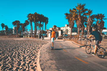 Young man riding a one wheel down the Venice beach in Los Angeles, California. Beautiful summer vibes.