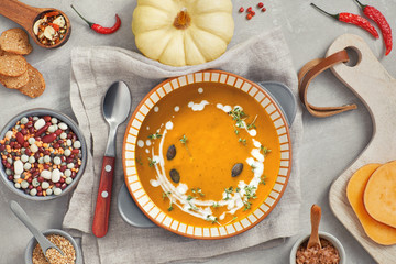 Pumpkin, mixed beans and sweet potato creme soup in ceramic bowl, top view with ingredients and spices