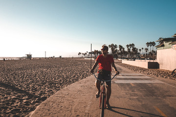 August 10, 2018. Los Angeles, USA. Venice beach vibes. People riding one wheel, bicycles and skateboards down the beach and palms. Summer spirit.