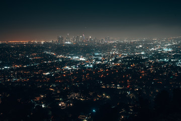 Beautiful super wide-angle night aerial view of Los Angeles, California, USA, with downtown district and mountains with sky full of stars and milky way, seen from the Griffith Park observatory.