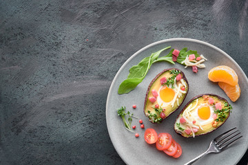Keto diet dish: Avocado boats with ham cubes, quail eggs, cheese on dark with copy-space