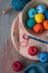 Top view of various yarn balls and latch hook on textured background