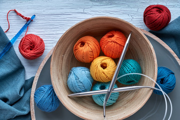 Top view of various yarn balls and latch hook on textured