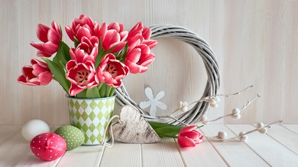 Springtime background with pink stripy tulups, Easter eggs, wooden heart and wattled wreath on light wood
